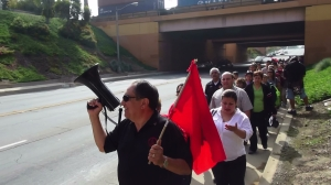Gilberto Esquivel, LANET member and also President of LULAC Council 3190, hoists the bullhorn as he holds the flag of the Farmworkers Union